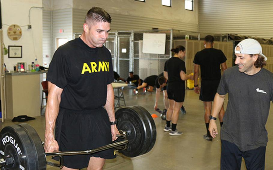 Maj. Timothy Cox lifts weights during physical training while the lead strength coach of 22nd Chemical Battalion, Mike Edwards, supervises him in the fitness training facility at Fort Bliss, Texas. Cox set a new standard by obtaining a 600, the highest score ever recorded, on the Army Combat Fitness Test.