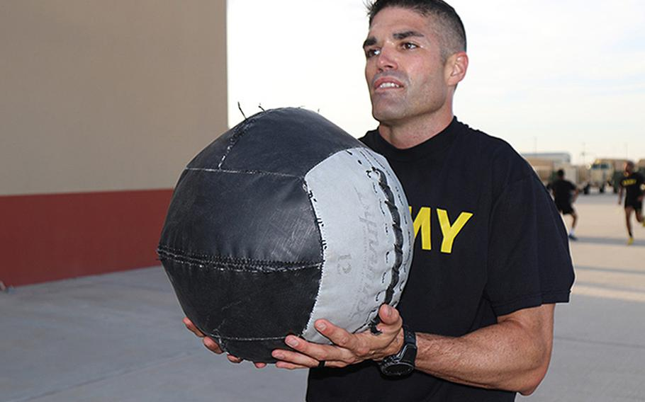Maj. Timothy Cox throws medicine balls during a morning physical training session at Fort Bliss, Texas, as he practices for the Army Combat Fitness Test. Cox set a new standard by obtaining a 600, the highest score ever recorded, on the Army Combat Fitness Test.