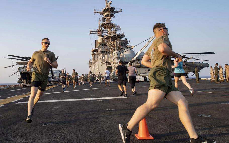 Sailors and Marines aboard amphibious assault ship USS Boxer run during a Labor Day 5K held on the flight deck during exercise Eager Lion in the Red Sea, Sept. 1, 2019. The Marines were the leanest service last year, whereas the Navy was the fattest, according to a Pentagon study.
