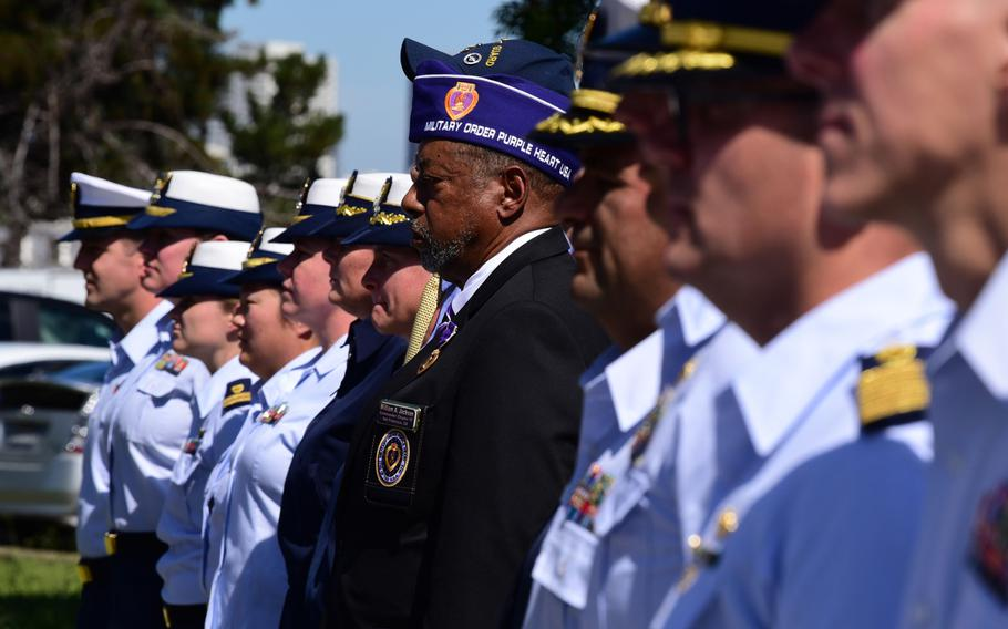 Servicemembers and guests stand during a ceremony on Coast Guard Island in Alameda, Calif., Sept. 3, 2019, where the service posthumously presented Purple Heart medals to families of two Coast Guardsmen who died when the Coast Guard Cutter Tampa was sunk by a German U-boat in Sept. 1918.
