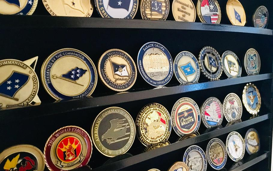 A display case features command and flag officer coins. The origin of commanders presenting coins to deserving sailors is disputed, but some historians think the tradition in U.S. history stems from the U.S. Civil War.