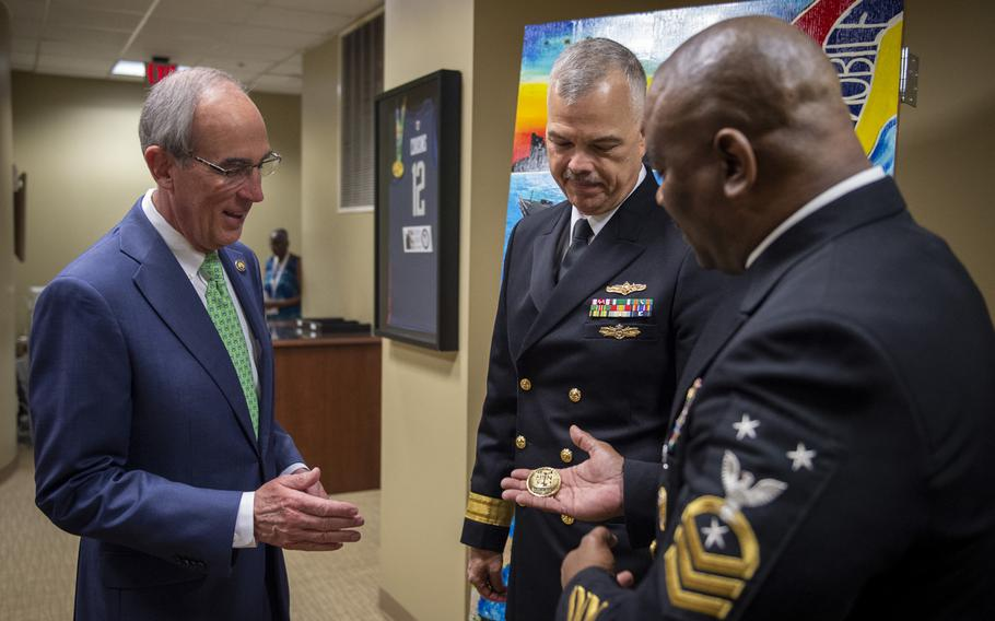 Command Master Chief of Program Executive of Ships and SEA 21, Antonio D. Perryman, right, from Mobile, Ala., presents Mobile Mayor Sandy Stimpson, left, with an official command challenge coin as Rear Adm. Ronald R. Fritzemeier, chief engineer of Space and Naval Warfare Command, looks on during the first day of Mobile Navy Week in February 2019.