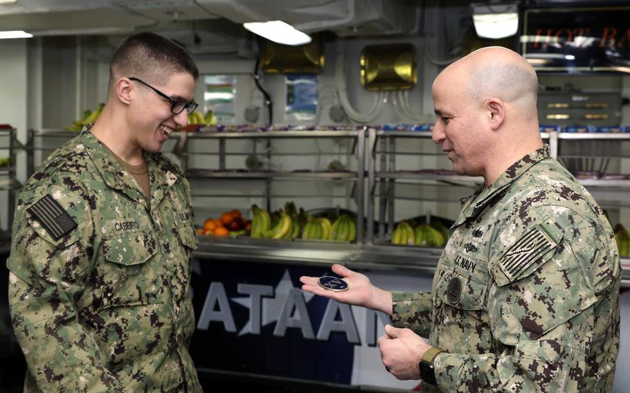 Master Chief Petty Officer of the Navy Russell Smith presents Petty Officer 3rd Class Angel Cabeiro with a coin in recognition for being selected as Bataan's Junior Sailor of the Year in January 2018. Bataan is homeported in Norfolk, Va.