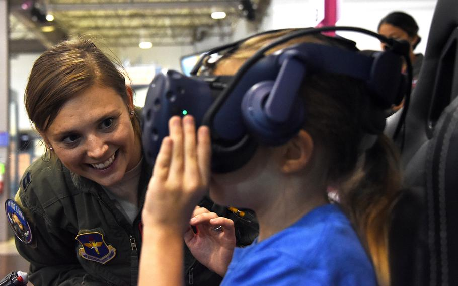An Air Force women's fly-in participant guides a girl through a flight simulator at the Girls in Aviation Day event hosted by the North Texas Chapter of Women in Aviation International at the Frontiers of Flight Museum in Dallas, Texas, Sept. 21, 2019.