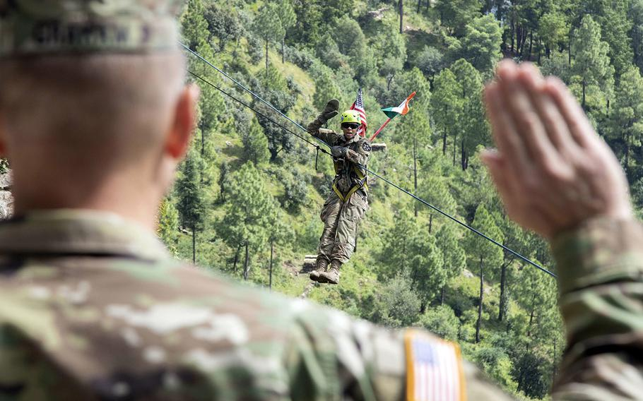 Army Spc. Sierra Hill, of 1-2 Stryker Brigade Combat Team, takes the oath of enlistment on a zipline at Chaubattia Military Station, India, Sept. 25, 2018, during Exercise Yudh Abhyas.