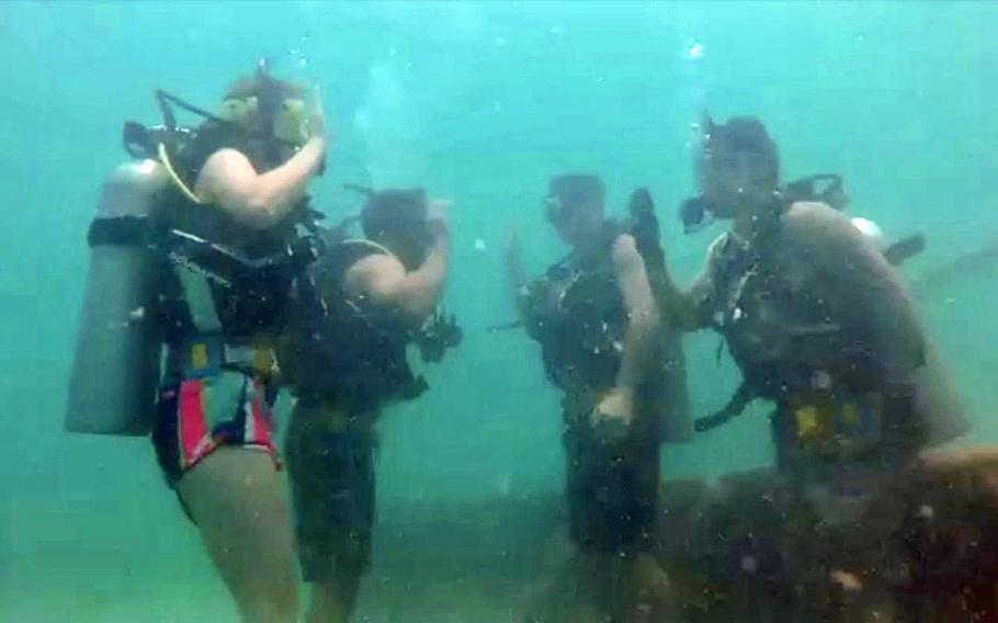 Petty Officer 2nd Class Gabriel Kastner and Petty Officer 3rd Class Ian Schlueter take the re-enlistment oath while scuba diving 2 miles off the coast of Bahrain, May 25, 2019.