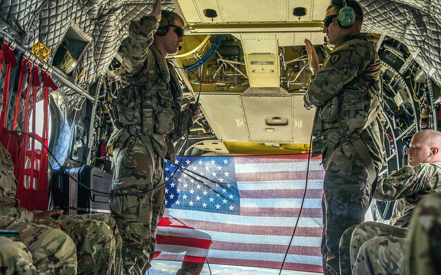 Sgt. Damian Childress, assigned to the U.S. Army 25th Infantry Division, re-enlists inside a CH-47 Chinook helicopter as it flies over the island of Oahu, Hawaii, Aug 13, 2019.