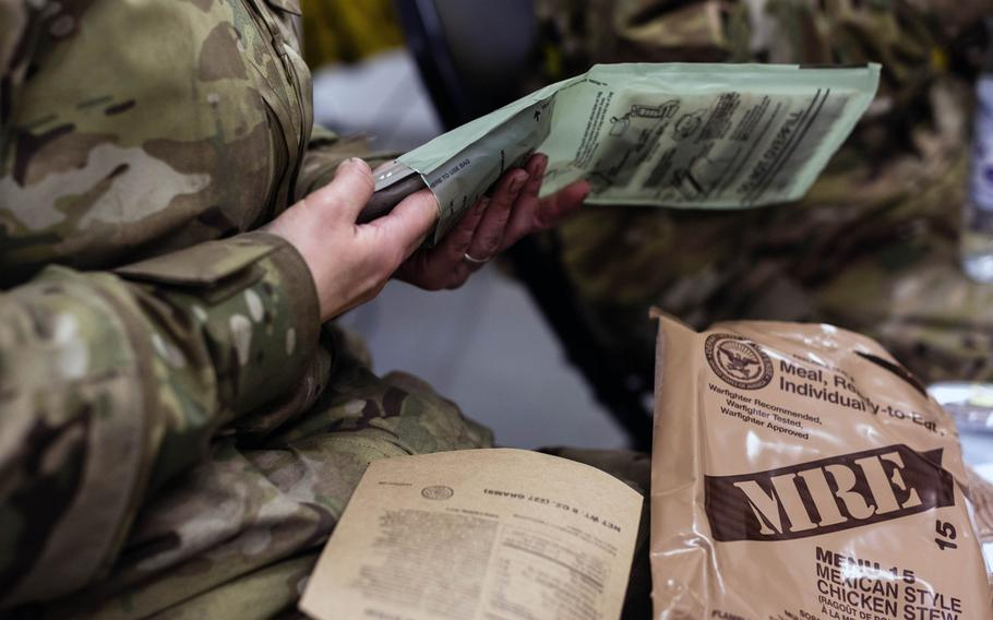 A U.S. airman with the 24th Intelligence Squadron opens his Meal, Ready to Eat while participating in exercise Contested Forge '18 at Grostenquin Air Base, France, in December 2018.