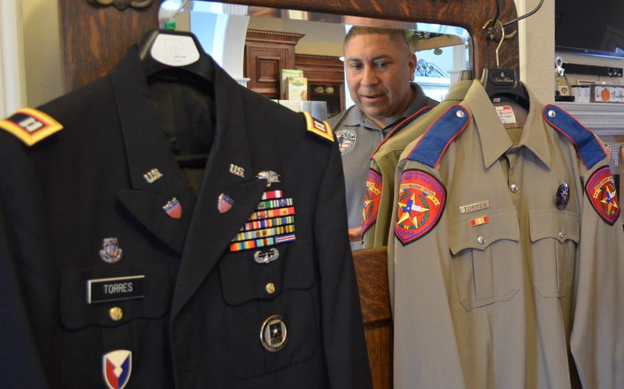 Le Roy Torres looks at the two uniforms that defined his adult life — his final dress uniform from 23 years in the Army and Army Reserve, from which he medically retired as a captain, and the final uniform he wore during his 14 years as a Texas state trooper. Torres sued the state of Texas in 2017 because he believes he was forced out of his job as a trooper due to injuries he sustained on deployment.