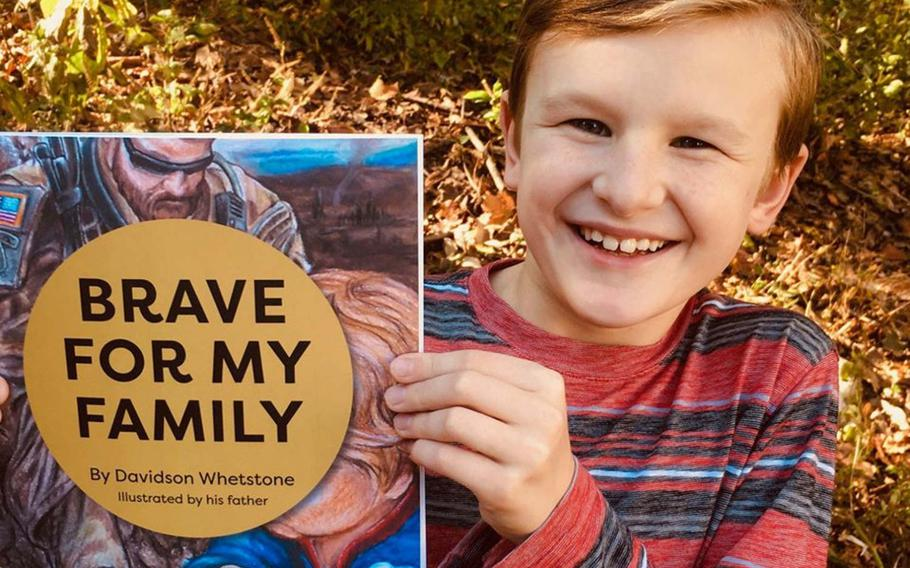 Young author Davidson Whetstone is pictured with his book ''Brave for My Family,'' illustrated by his Green Beret father, which was published in early November. The 9-year-old hopes the book will help other military children not be scared when their parents deploy to war zones.