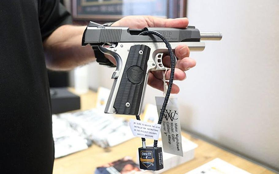 A pistol with a cable safety lock. The Air Force is distributing about 150,000 gun safety locks to bases in the U.S. as part of efforts to reduce suicides and accidental deaths, the service said.