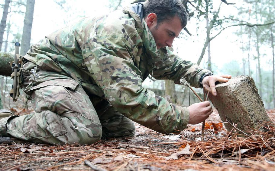 A student from the U.S. Army John F. Kennedy Special Warfare Center and School practices setting a trap for small game during the survival phase of Survival, Evasion, Resistance and Escape Level-C training at Camp Mackall, N.C., in February 2019. More than 100 troops participating in the present course have been quarantined this week, after most of them tested positive for COVID-19.