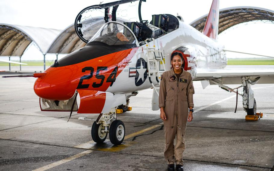 Student naval aviator Lt. j.g. Madeline Swegle, assigned to the Redhawks of Training Squadron (VT) 21 at Naval Air Station Kingsville, Texas, stands by a T-45C Goshawk training aircraft following her final flight to complete the undergraduate Tactical Air (Strike) pilot training syllabus, July 7, 2020. Swegle is the Navy's first known Black female strike aviator and will receive her wings during a ceremony July 31.
