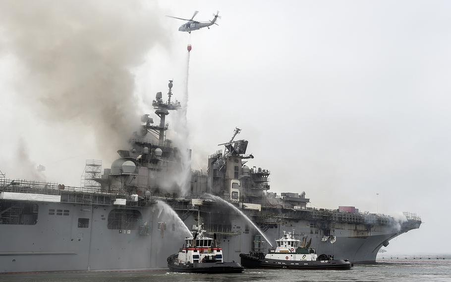 Firefighters and an aircraft from Helicopter Sea Combat Squadron 3 battle a blaze aboard the amphibious assault ship USS Bonhomme Richard at Naval Base San Diego, Calif., Monday, July 13, 2020.