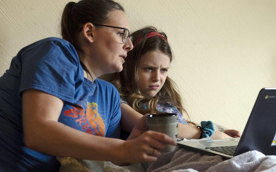 A mother and daughter read over a school assignment inside their home at Kaiserslautern, Germany, April 14, 2020.