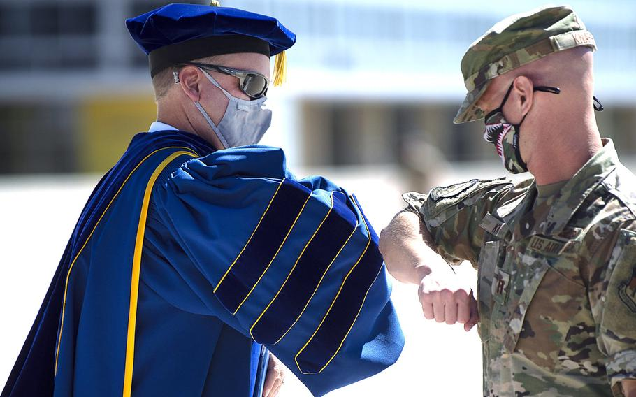 An Air Force Academy cadet bumps elbows with a member of faculty at the academy's first-ever convocation ceremony on Aug. 2, 2020 to mark the beginning of the academic year. Two weeks later, despite the academy taking numerous precautions to stem the spread of the coronavirus, an unspecified number of cadets tested positive for it.