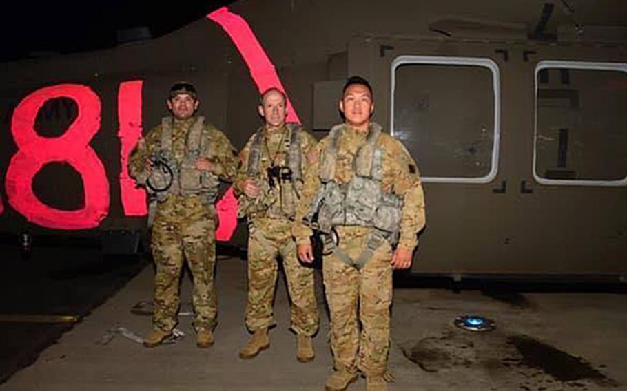 The California Army National Guard UH-60 Black Hawk helicopter crew from the 40th Combat Aviation Brigade that flew dozens to safety from the Creek Fire poses for photoon Sept. 5, 2020. From left, pilot Chief Warrant Officer 2 Irvin Hernandez, pilot-in-command Chief Warrant Officer 5 Kipp Goding, and crew chief Warrant Officer 1 Ge Xiong.