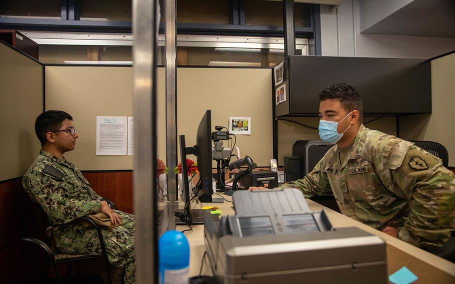 Pvt. Aaron Byrd, right, of the 25th Division Sustainment Brigade, helps Petty Officer 2nd Class Nick Ishiharapuzon get a new Common Access Card at the Soldier Support Center at Schofield Barracks, Hawaii, Aug. 20, 2020.
