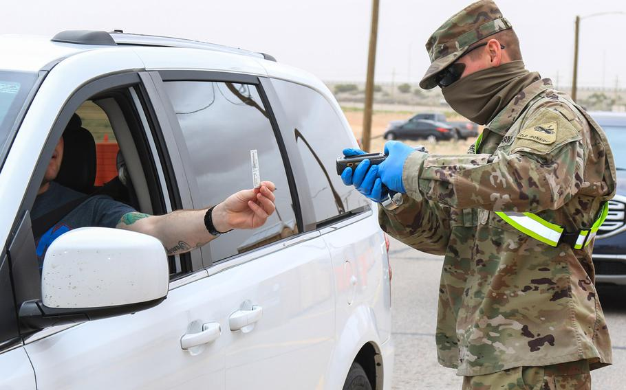 Pfc. Ryan Chisholm checks an ID at Fort Bliss, Texas, March 27, 2020. Service members and others with Common Access Cards that expired during the coronavirus pandemic or are about to expire must renew them by September 30, Defense Department guidance issued this month said.