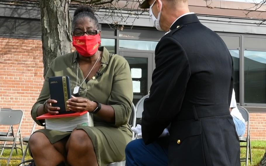 A U.S. Marine Corps major with 4th Combat Engineer Battalion presents Lance Cpl. Corey Staten's mother, Nancy Staten, the Navy and Marine Corps Medal during an award ceremony in Baltimore, Md., Oct. 24, 2020. Lance Cpl. Staten was awarded the medal for saving another Marine's life in 2018.