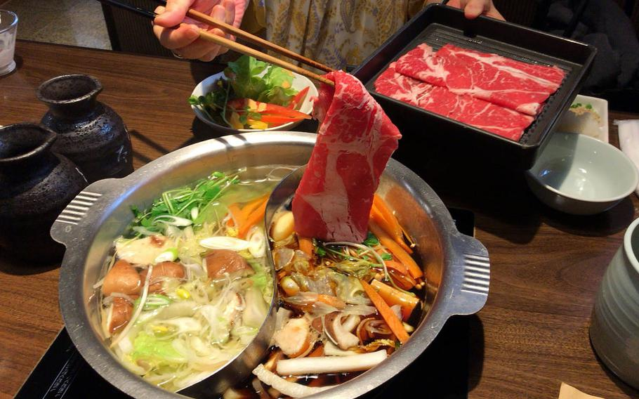 Beef, pork and vegetables are cooked in the hot pot with sukiyaki and shabu shabu soup at Nabezo in Shibuya, Tokyo.