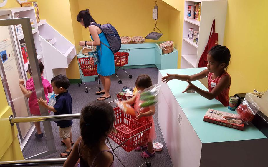 """Young grocery shoppers jockey for position at a store in """"Your Town,"""" an interactive display at Hawaii Children's Discovery Center in Honolulu."""