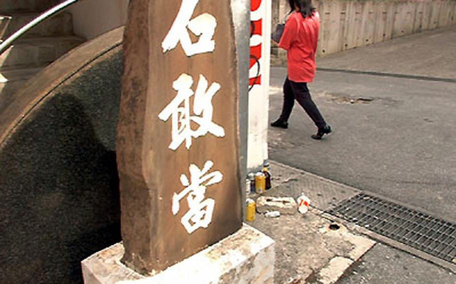 """An Ishi-Gan-To stone marker stands on a corner of a condominium in Naha. Okinawans believe that evil spirits dwell in dead ends and street corners. The three Chinese characters are """"magic"""" words to deflect the devil."""