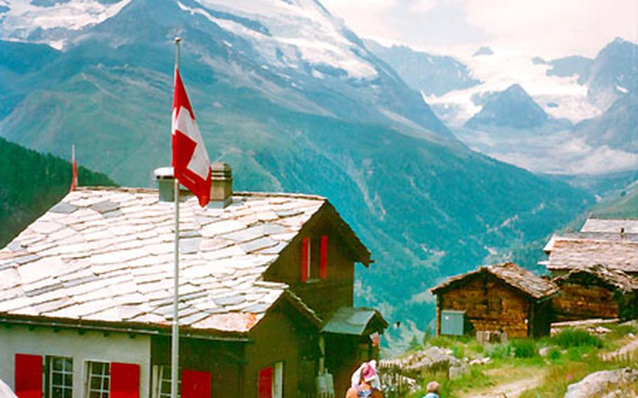 Hikers pass a mountain hut flying the Swiss flag under the mighty Matterhorn. When the weather is good, between 100 and 200 climbers try to ascend the Matterhorn every day. But at any time of year, Zermatt, Switzerland, is known for outdoor activities.