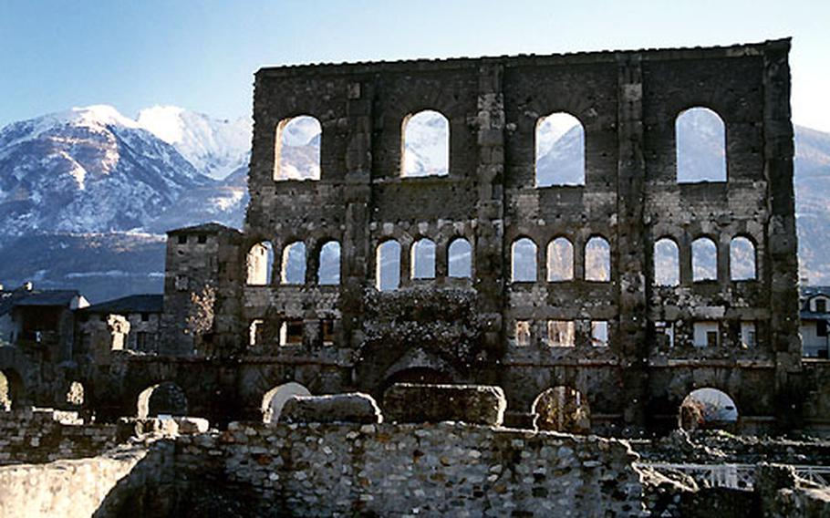 Part of the facade of Aosta's Roman theater towers above the ruins of an amphitheater, which once offered covered seating for spectators in the first century B.C.