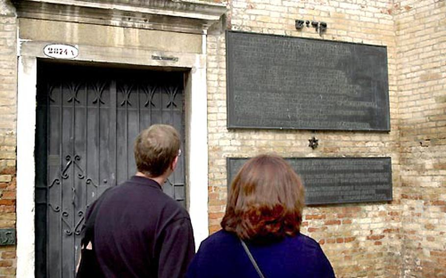 Tourists read a plaque on a wall of the Venice Ghetto remembering the Holocaust and the arrest and deportation of Venice Jews on Dec.5, 1943, and Aug. 17, 1944.