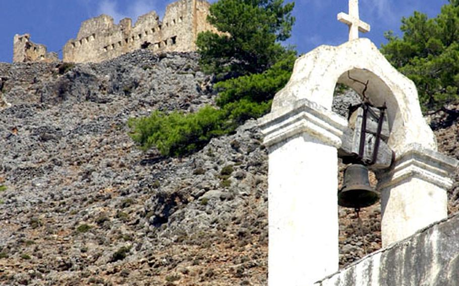 The ruins of a castle tower over the bell tower of a Greek Orthodox chapel at Agia Roumeli are visible on the way to or from the Samaria Gorge.