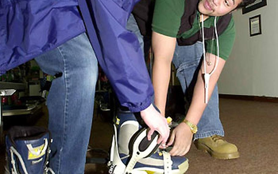 Joel Dawson, left, adjusts his snowboard bindings with the help of Josh Faiai, a recreation aide at the Outdoor Recreation Center, Misawa Air Base, Japan. The center rents snowboards and skis, and offers equipment fittings and trips to area ski resorts.