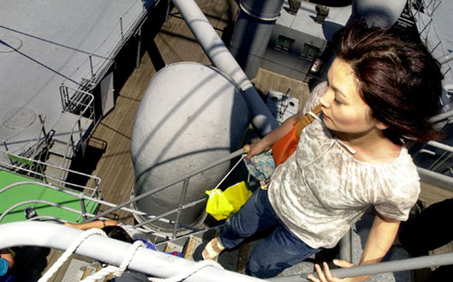 A Japanese visitor attempts to get a bird's-eye view of Yokosuka city from the mast of the Mikasa.