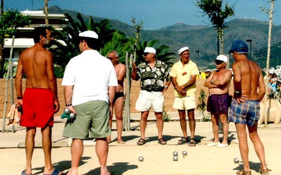 Costa Brava tourists enjoy a game of boule on the beach at Roses, Spain.