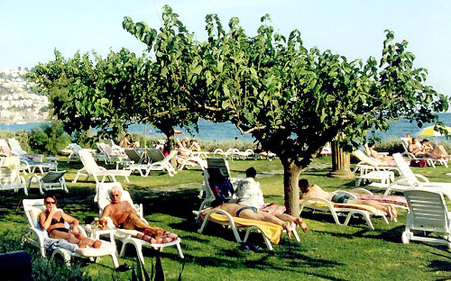 The beach hotel Coral Platja in Roses has a grassy area for sunning and lounging.