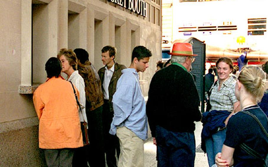 Patrons line up outside the Half Price Ticket Booth on London's Leicester Square.