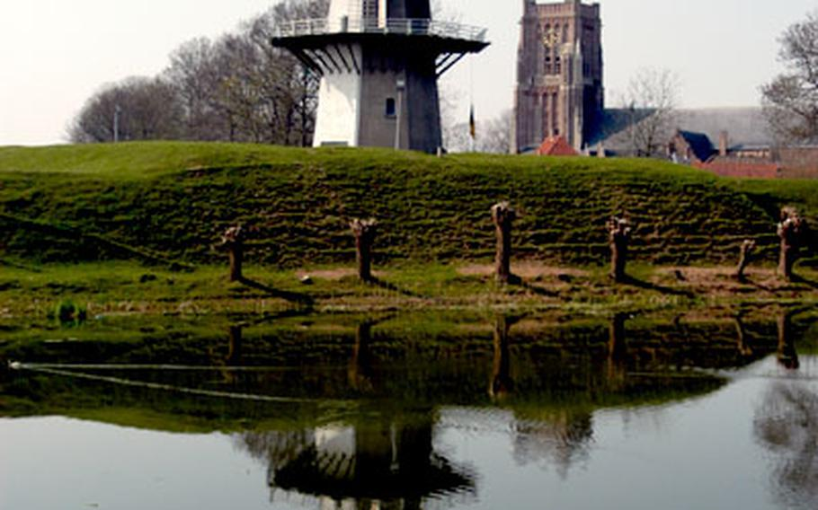 Woudrichem's windmill and Martinus church are reflected in the moat on the south side of this Dutch medieval town.