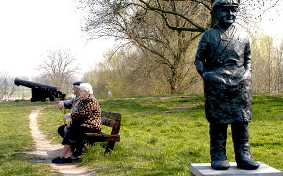 An elderly couple sit on a bench atop Woudrichem's ramparts watching the ships ply the Waal river. In the foreground is a statue known as the Zalmvisser, or salmon fisher. Fishing was once a mainstay of the locals, but unfortunately there are no salmon left in Dutch rivers. In the background at far left is Loevestein Castle, across the Maas river from Woudrichem.