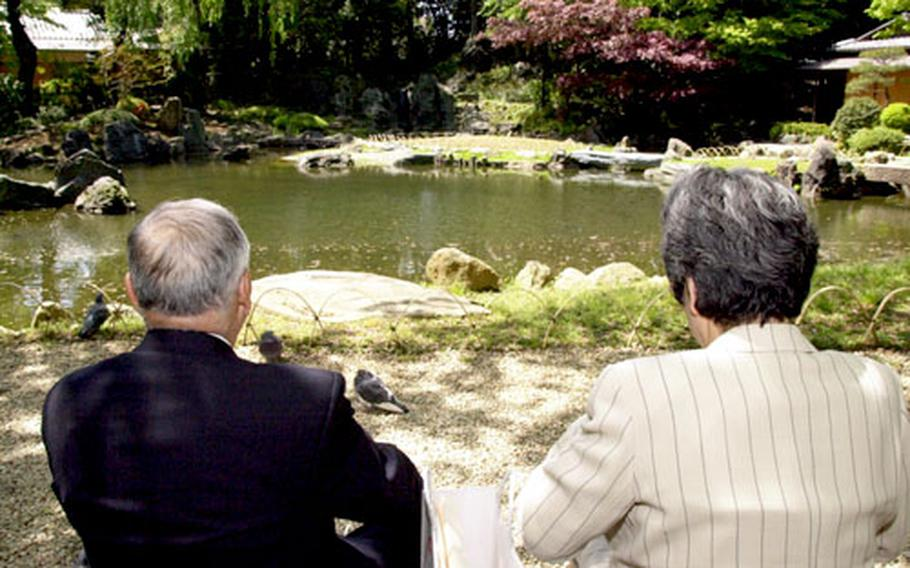 A Japanese couple enjoys the afternoon next to a pond at the Yasukuni Shrine in Tokyo. The pool of water was built and dedicated to those who died of thirst on battlefields.