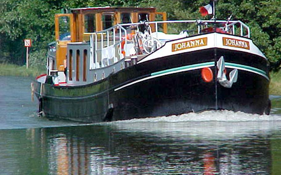 Formerly a dredger and carrier of carnival equipment, the 80-foot, 60-ton canal boat Johanna was converted in 1992 to a passenger barge. Here, she cruises near Germany in the French Alsace region. The Johanna has its own captain and mate who do most of the nautical work, leaving passengers to enjoy themselves.