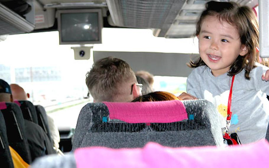 Three-year-old Katie Sizemore, whose father is stationed at Schweinfurt, Germany, had a grand time entertaining the other bus passengers.