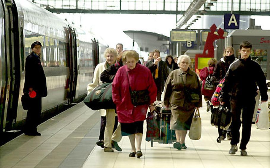Passengers disembark at the main train station in Frankfurt, Germany.