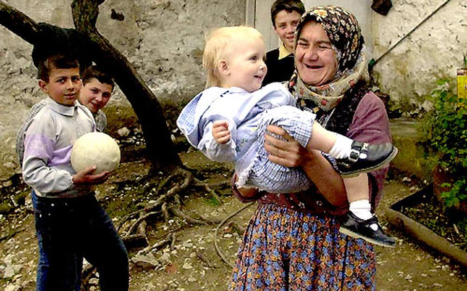 """Why deprive your kids of interesting cultural experiences just because they're not adults? Children tend to adapt readily if visiting """"exotic"""" villages and cultures becomes routine. Here Lale Boyd, 18 months, makes friends with a village woman near Bergama in Turkey."""