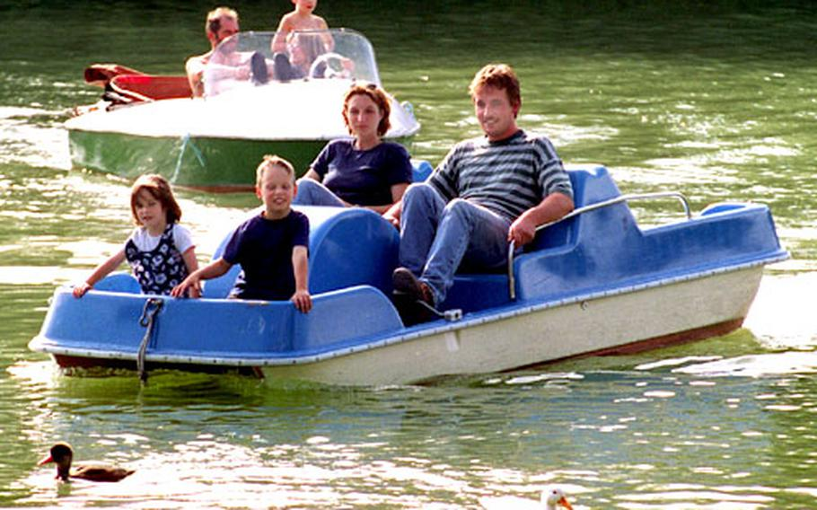 Families enjoy a summer day on the Kleinhesselohersee in Munich, Germany's English Garden. Working something into the travel schedule just for kids will keep the whole family happy.