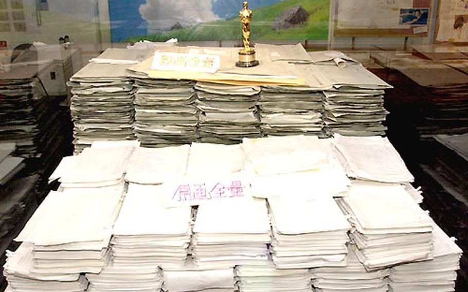 """Atop the large pile of raw sketches for the movie """"Spirited Away"""" sits the Oscar the movie won for """"Best Animated Feature Film."""""""