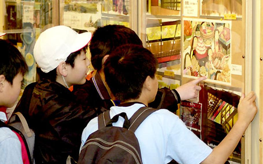 """Japanese schoolboys on a day trip to the museum look at the many drawings and animation cells used in the movie """"Spirited Away."""""""