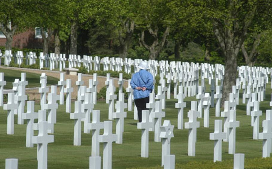 A visitor walks among the grave markers at Cambridge American Cemetery in England. More than 3,800 American war dead from World War II are buried at the cemetery near Cambridge, England.