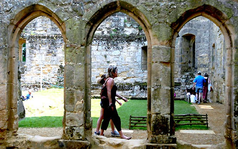 Visitors walk among the ruins inside the mighty walls of Bodiam Castle in the south of England.