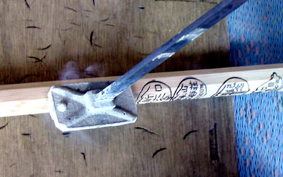 A climbing stick is branded at one of the resting stations on Mount Fuji. Many climbers purchase the sticks and keep them as souvenirs.