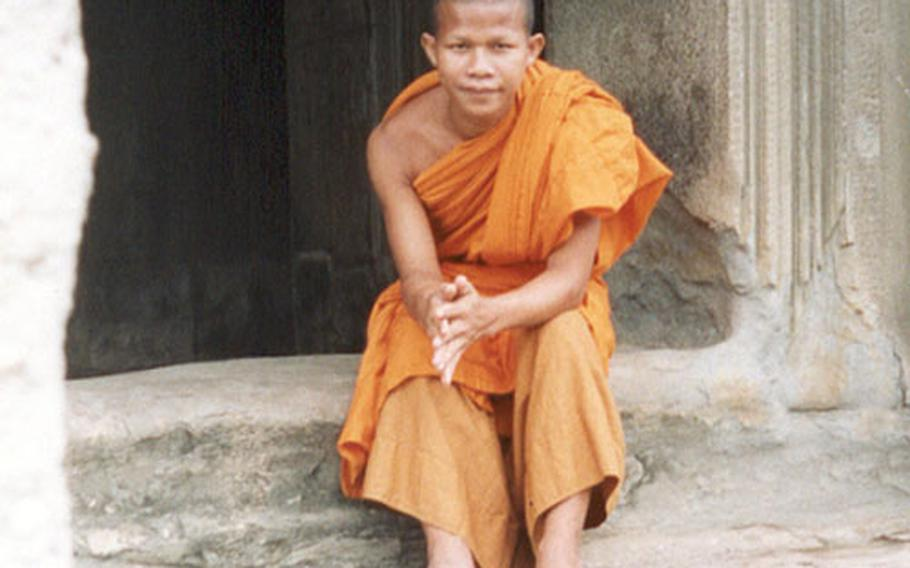 Meas, a 22-year-old Buddhist, sits on the steps on part of Angkor Wat.